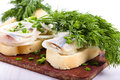 Sandwiches of white bread with herring onions and herbs on wooden board Stock Photos