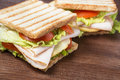 Sandwiches on wooden table with chicken breast salad cheese and tomatoes Stock Photo