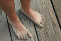 Sandy bare feet barefoot covered in sand on the boardwalk Stock Photo