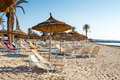 Sandy beach with deckchairs and parasols at sunset Stock Image