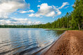 Beautiful deserted sandy beach of a forest lake with sun beds and a pier for fishing in the sun