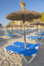 Sandy beach with straw umbrellas and sunbeds beautiful at sunrise in paguera majorca balearic islands spain Royalty Free Stock Photography