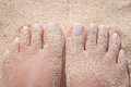Sandy feet on the beach of a young woman partially covered with sand Royalty Free Stock Image