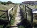 Sandy footpath to beach a leading a beautiful on a sunny summer day flanked with wooden and wired fencing Stock Image