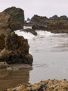 Sandy ocean beach with rock outcrops Royalty Free Stock Photo