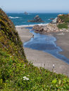 Sandy ocean beach with rock outcrops Stock Images