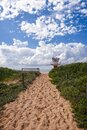 Sandy pathway to the beach patrol tower clouds Royalty Free Stock Photo