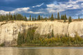 Sandy river bank cliff along with pine trees and storm clouds in sky Royalty Free Stock Images