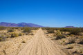 Sandy road in the mojave desert sand leads straight into distance middle of Royalty Free Stock Photography