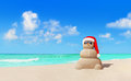 Sandy snowman in Christmas Santa hat and sunglasses at beach Royalty Free Stock Photo