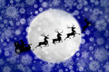 Santa against moon in snowfall Stock Image