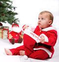 Santa baby boy sitting next to christmas tree studio shoot on white background Stock Photos