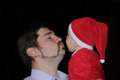 Santa baby father kissing his claus Royalty Free Stock Photos
