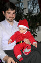 Santa baby little sitting by his father Royalty Free Stock Images