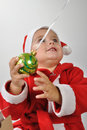 Santa baby playing with a Christmas ball Stock Images