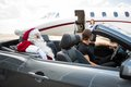 Santa and chauffeur in convertible while airhostess standing against private jet Stock Photo
