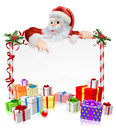 Santa christmas gifts sign illustration with peeking over a surrounded by stacks of Stock Photography