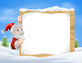 Santa christmas sign snow scene in the centre of a winter with capped trees Stock Photos