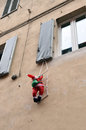 Santa claus with a bag of gifts on rope ladder climbs in the window house Royalty Free Stock Images
