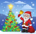 Santa Claus with bell by Christmas tree Royalty Free Stock Photo