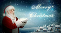 "Santa claus blowing snow ""merry christmas"" from to little town Stock Photography"