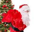 Santa claus carrying sack by christmas tree isolated Stock Photos