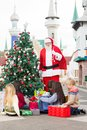 Santa claus with children opening presents by christmas tree in courtyard Royalty Free Stock Images