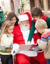 Santa claus and children reading book Photographie stock libre de droits
