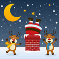 Santa claus in the chimney with reindeer stuck a two cute christmas laughing a snowy scene moon and stars eps file Stock Photos