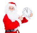 Santa claus with clock pointing at showing time over white background Royalty Free Stock Images