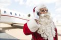 Santa claus communicating on mobile phone against private jet at airport terminal Royalty Free Stock Photo