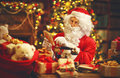 Santa Claus at desk with letters,   gifts near Christmas tree Royalty Free Stock Photo
