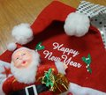 Santa Claus doll and white Happy New Year message on red Santa hat Royalty Free Stock Photo