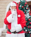 Santa claus with finger on lips contra la navidad Fotos de archivo