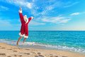 Santa Claus flying against sea beach - Christmas concept Royalty Free Stock Photo