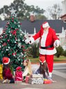 Santa claus gesturing at children by christmas decorated tree in courtyard Stock Photography