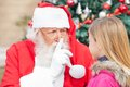 Santa claus gesturing finger on lips beim schauen Stockbild