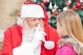 Santa claus gesturing finger on lips mientras que mira Imagen de archivo