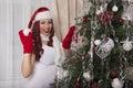 Santa Claus girl decorating christmas tree at home. Beautiful smiling Royalty Free Stock Photo