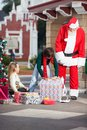 Santa claus and girl looking at boy opening gift christmas in courtyard Royalty Free Stock Photos