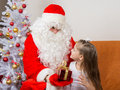 Santa Claus gives gift a five-year girl Royalty Free Stock Photo