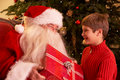 Santa Claus Giving Gift To Boy In Front Of Christm Stock Photos