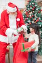 Santa claus giving gifts to girl Arkivbilder
