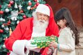 Santa claus giving present to girl Stock Foto's