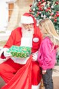 Santa claus giving present to girl Fotografia Stock Libera da Diritti