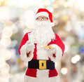 Santa claus with glass of milk and cookies christmas holidays food drink people concept man in costume over lights Stock Image