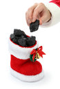 Santa claus has put coal in the stocking hand of christmas present for bad boys and bad girls Royalty Free Stock Photos