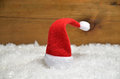 Santa claus hat wooden background in snow christmas decoration Stock Photography