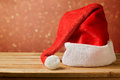 Santa claus hat on wooden table over bokeh background red Royalty Free Stock Images
