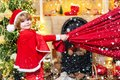 Santa Claus helper carrying big bag full of gifts. Santa helper holding a red bag with presents. Dreamy toddler on Royalty Free Stock Photo